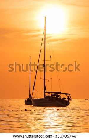Yacht in the sea at sunset hot yellow light - seascape background, vertical shot - stock photo