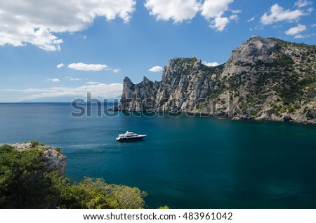 Yacht in the sea on blue sky background. Top view of Blue Bay and the mountains on the Black sea coast. Royal Beach, Crimea.