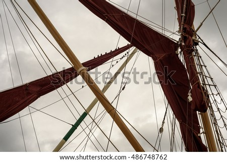 Yacht masts and rigging set against a rain filled sky