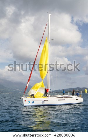 """Yacht on the background of the cloudy sky. Tivat, Montenegro - 28 April, 2016 Regatta """"Russian stream"""" in God-Katorskaya bay of the Adriatic Sea off the coast of Montenegro. - stock photo"""