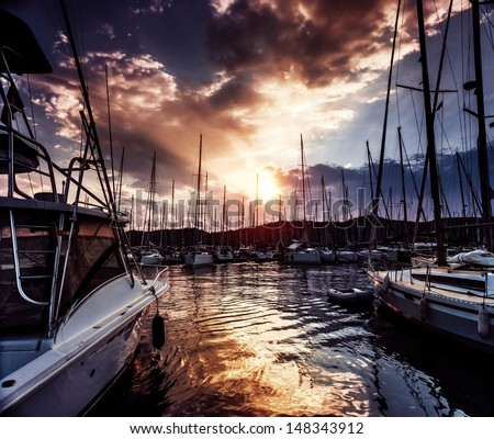 Yacht port on dramatic sunset background, mysterious cloudscape, active lifestyle, luxury water transport, summer sport, travel and tourism concept - stock photo