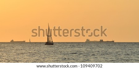 yacht sailing against huge cargo ship at the sunset - stock photo