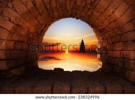 Yacht sailing against sunset - stock photo