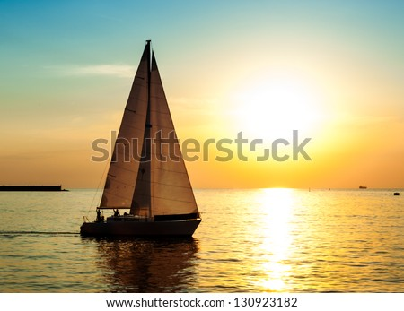 Yacht sailing against sunset. Holiday lifestyle landscape with skyline sailboat and sunset silhouette. Yachting tourism - maritime evening walk. Romantic trip on luxury yacht during the sea sunset. - stock photo