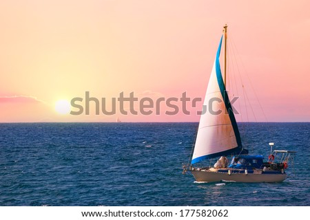 Yacht sailing in the sea at sunrise