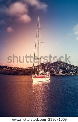 Yacht sailing next to rocks in Antarctica - stock photo