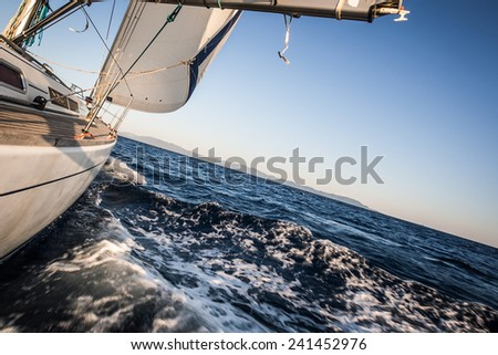 Yacht sailing on sea towards coast - stock photo