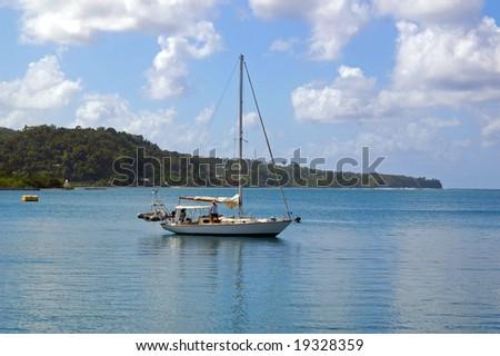 yacht sailing onto tropical harbor - stock photo
