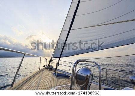 Yacht sailing to the sunset - stock photo