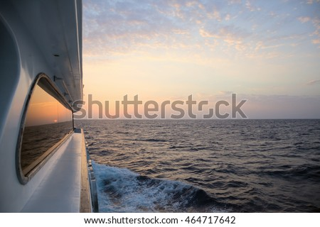 Yacht sailing towards the sunrise