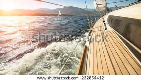 Yacht sailing towards the sunset. Sailing. Luxury yachts. - stock photo