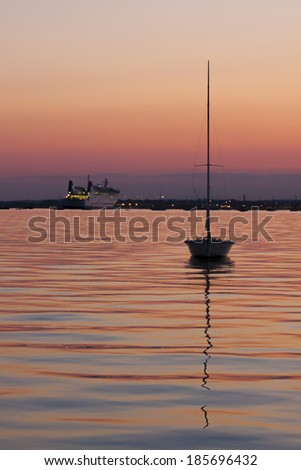 Yacht silhouetted against a pink and purple sky on calm seas inside Poole harbor with the cross-channel ferry in the distance