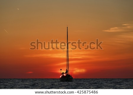 Yacht silhouetted at beautiful sunset