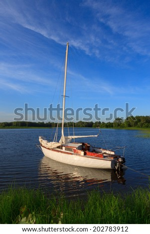 yacht standing by the shore on still water - stock photo