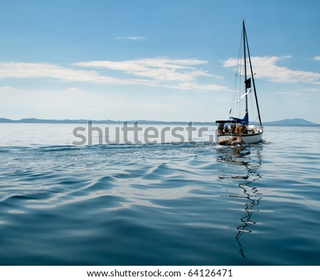 Yacht with trailing dinghy on the calm seas of the Mediterranean - stock photo