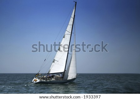 Yacht with white sails in dark blue open space. The good wind fills sails. - stock photo