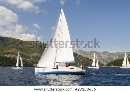 """Yacht with white sails on a background of mountains. Tivat, Montenegro - 26 April, 2016. Regatta """"Russian stream"""" in God-Katorskaya bay of the Adriatic Sea off the coast of Montenegro. - stock photo"""