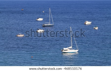 Yachts and boats in the Mediterranean Sea captured from a distance, the city of Menton, France.