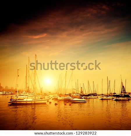 Yachts and pier at dusk - stock photo