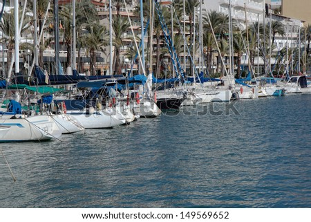 Yachts in the Mediterranean port of Palma city (Mallorca) with palms and buildings of promenade in the background and reflections on the water surface