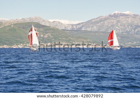 """Yachts on the background of the mountain shore. Tivat, Montenegro - 26 April, 2016 Regatta """"Russian stream"""" in God-Katorskaya bay of the Adriatic Sea off the coast of Montenegro. - stock photo"""