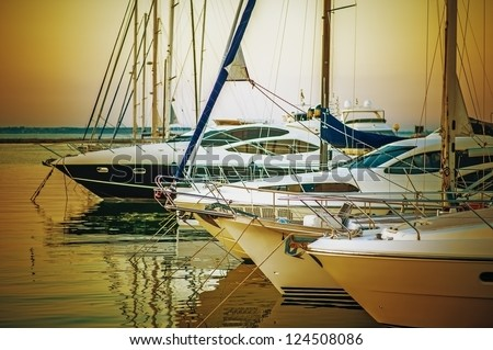 Yachts parked on mooring, in evening sunset. - stock photo