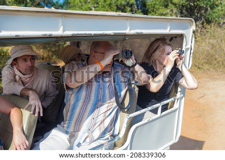 YALA NATIONAL PARK, SRI LANKA - MARCH 4, 2014: Tourists looking through binoculars during safari tour in the Yala park. Yala is the second largest national park in Sri Lanka. - stock photo