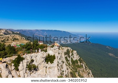 YALTA, RUSSIA - SEPTEMBER 19, 2015: People looking at Black sea coast panorama from view point on Ai-Petri mount, famous natural landmark