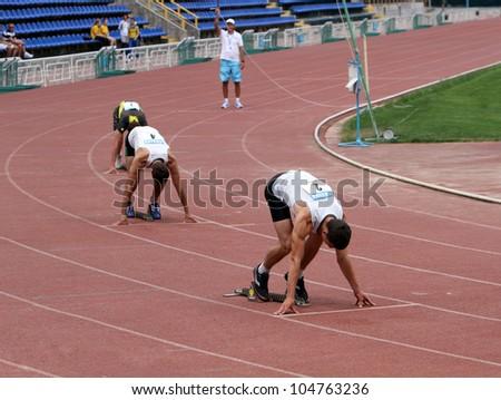 YALTA, UKRAINE - MAY 24: Unidentified boys age 16-17 on the start of the 400 meters race of the international athletic meet between Ukraine, Turkey, Belarus on May 24, 2012 in Yalta, Ukraine - stock photo