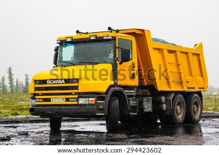 YAMAL, RUSSIA - JULY 4, 2015: Yellow dump truck Scania T360 at the interurban road. - stock photo