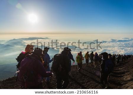 YAMANASHI, JAPAN - JULY 27: Hikers gather during sunrise on the Mt. Fuji summit on July 27, 2014 in Yamanashi, Japan - stock photo