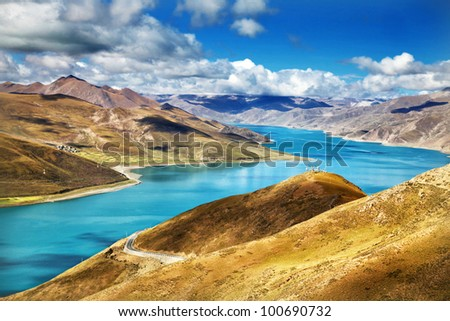 Yamdrok-tso lake shines on sunny blue sky day in Tibet - stock photo