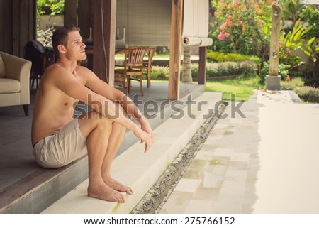 Yang man sitting on his luxury villa, thinking and relax  - stock photo