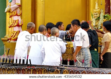 YANGON, MYANMAR - CIRCA FEBRUARY 2007: Nuns performing a religious ceremony in the Shwedagon Pagoda - stock photo