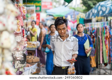 YANGON, MYANMAR - FEBRUARY 10: Burmese street scene in China town on February 10, 2014 in Yangon. Myanmar is ethnically diverse with 51 million inhabitants belonging to 135 ethnic groups. - stock photo