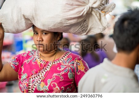 YANGON, MYANMAR - FEBRUARY 10: Burmese woman carries a heavy load in Chinatown on February 10, 2014 in Yangon. Myanmar is ethnically diverse with 51 million inhabitants belonging to 135 ethnic groups. - stock photo