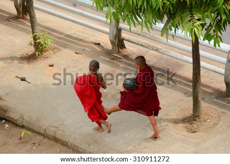 YANGON, MYANMAR - JANUARY 30, 2015. Buddhist novices who live in the monastery come out to receive food from donors in Yangon city, Myanmar.