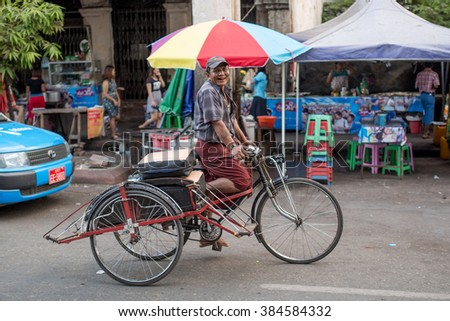 YANGON, MYANMAR - JANUARY 3, 2016: Unidentified man riding a trishaw on the streets of Yangon , Myanmar on January 3, 2016