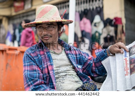 YANGON, MYANMAR - JANUARY 3, 2016: Unidentified trishaw driver on a break reading newspaper on the streets of Yangon , Myanmar on January 3, 2016