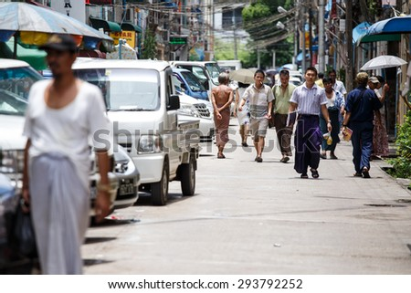 YANGON, MYANMAR - JUNE 12 2015: Local people walking on one of the hottest recorded days before monsoon season in Yangon, Myanmar. - stock photo