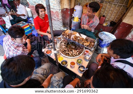 YANGON, MYANMAR - JUNE 12 2015: Locals eat pot street food on one of the hottest recorded days before monsoon season in Yangon, Myanmar. - stock photo
