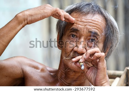 YANGON, MYANMAR - JUNE 12 2015: Old man smoking burmese cheroot cigar on one of the hottest recorded days before monsoon season in Yangon, Myanmar.