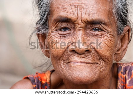 YANGON, MYANMAR - JUNE 12 2015: Older lady sits on the street on one of the hottest recorded days before monsoon season in Yangon, Myanmar. - stock photo