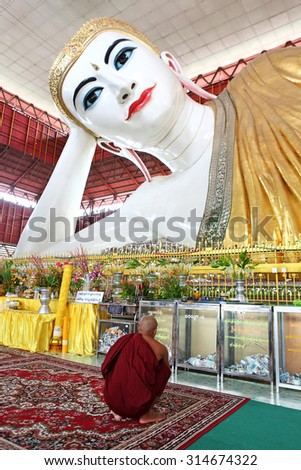 YANGON, MYANMAR - OCT 6: Buddhist monks are praying at Chauk Htat Gyi Reclining Buddha on October 6, 2012 in Yangon, Myanmar.The enormous reclining Buddha,  Buddha is 65 meters long