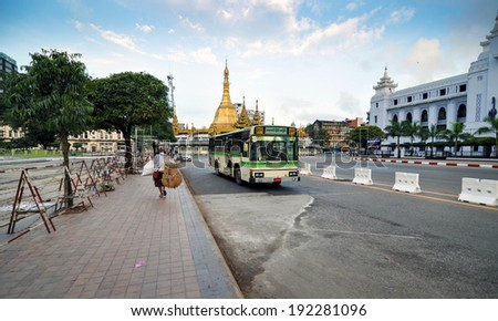 YANGON, MYANMAR - OCT 12, 2013: Traffic in downtown Yangon on October 12, 2013, in Yangon, Myanmar (or Burma). In the middle of a roundabout, stands the Sule Pagoda, a religious and historic site.