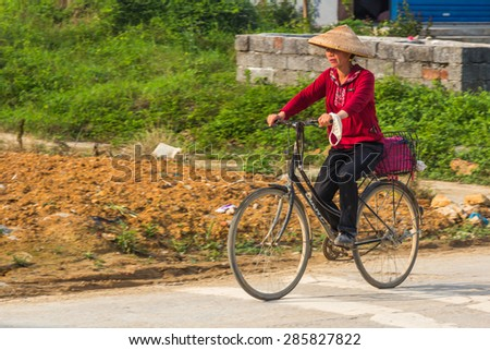 YANGSHUO, CHINA - MAY 01, 2015: An unidentified middle aged woman riding a bicycle in small village next to Yulong river. There are around 430 million of bicycle owners in China. - stock photo