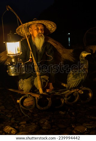 YANGSHUO, CHINA - OCTOBER 16: Chinese fisherman fishing with cormorants birds in Yangshuo, traditional fishing use trained cormorants to fish, October 16, 2013 Yangshuo in Guangxi, China - stock photo