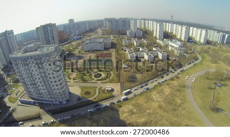Yard in a residential area with a playground against the cityscape, aerial view