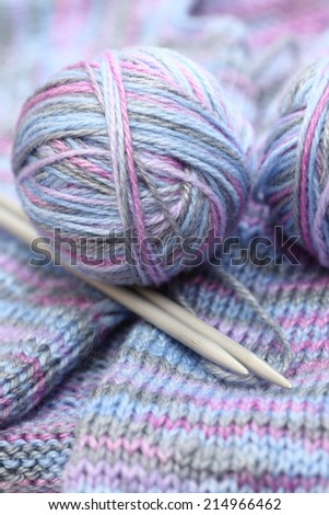 Yarn and knitting needles on a wool background.