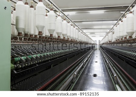 yarn spools on spinning machine in a textile factory - stock photo